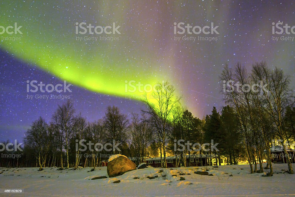 The northern lights glowing over the snowscape stock photo