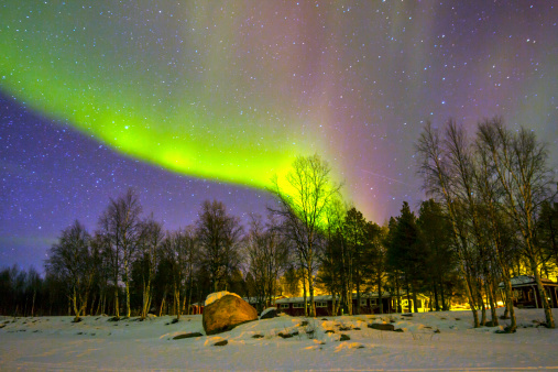 The Northern Lights Glowing Over The Snowscape Stock Photo - Download Image Now