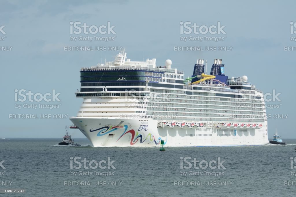 The Norwegian Epic escorted by tugboats. stock photo
