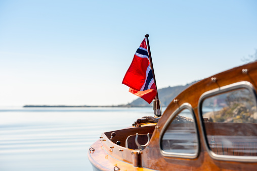 The norwegian flag in the aft mast of a wooden boat.