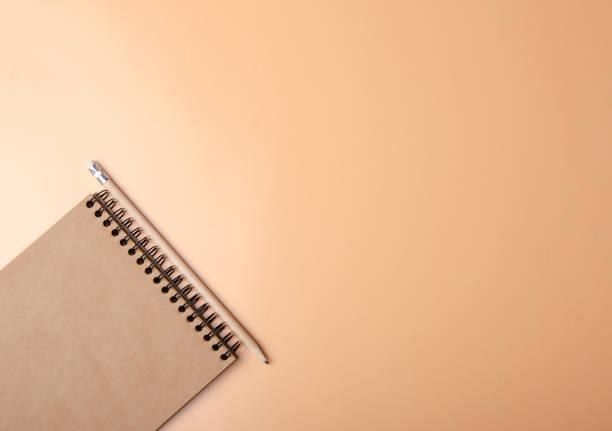 das notebook, bleistift auf farbe orange hintergrund - unterrichtsplanung vorlagen stock-fotos und bilder