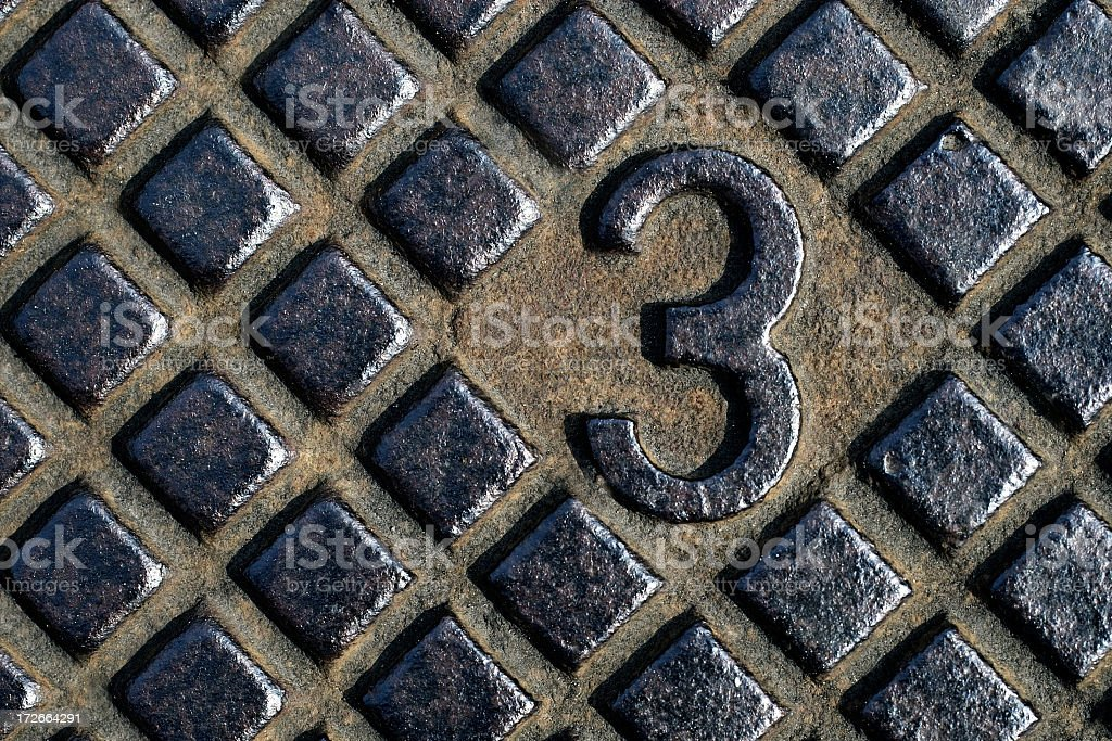 The number 3 cut out of a brass background  stock photo
