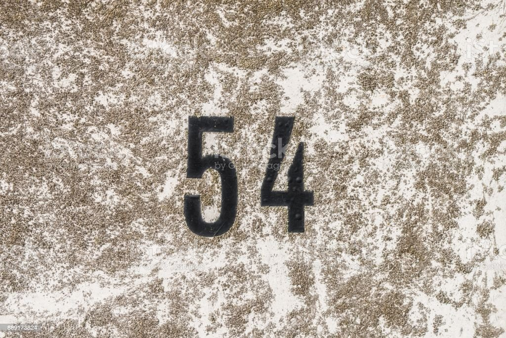 The Number 54, fifty four, on a surface with lichen stock photo