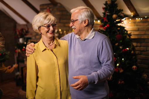 Senior couple hugging while posing for a photo on Christmas