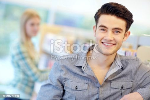 Handsome male student in a library with female friend in the background