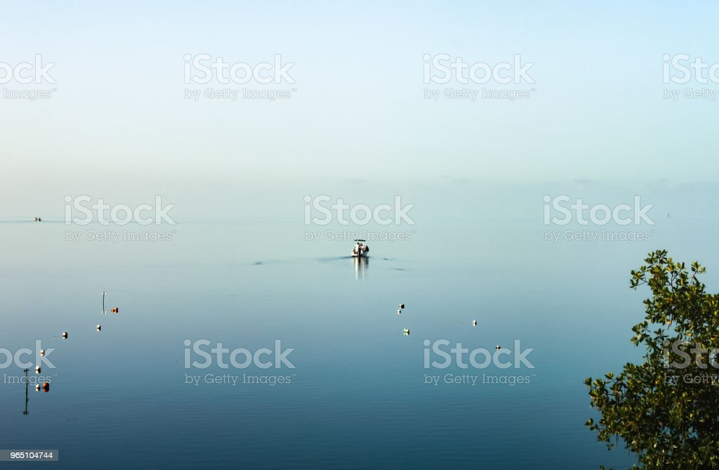 The ocean blend into the sky - a fishing boat heads out to sea on a dreamy calm overcast day when water and sky are the same pastel color royalty-free stock photo