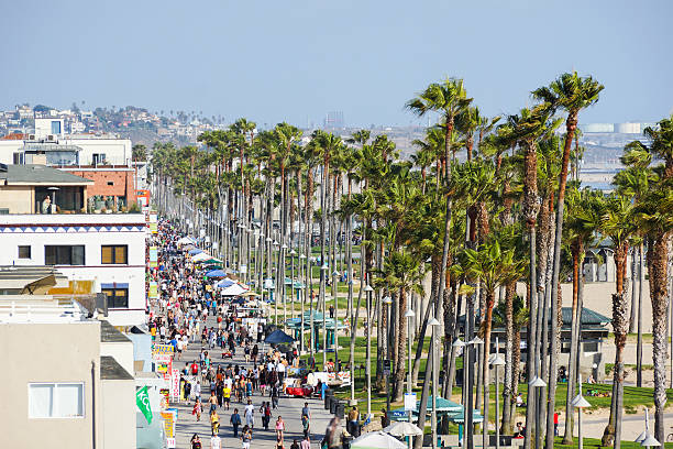 The Ocean Boardwalk at Venice Beach Many People at the Ocean Boardwalk in Venice Beach, Los Angeles County. It is a sunny day with blue sky. View from above. venice beach stock pictures, royalty-free photos & images