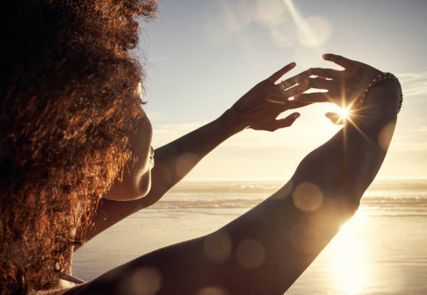 The ocean breeze brings a life of ease Rearview shot of a young woman blocking the sunlight with her hands at the beach sunlight stock pictures, royalty-free photos & images
