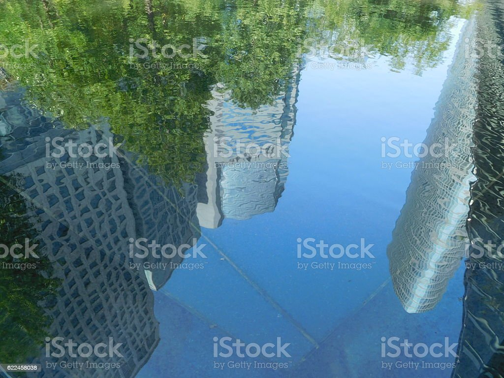 The office buildings reflected on the surface of water stock photo