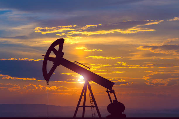 the oil pump on the background of the sunset - benzina foto e immagini stock