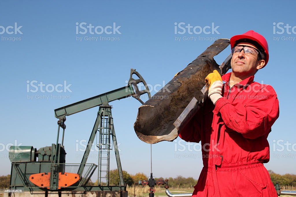 The Oilfield Worker At Well Pump Jack Site stock photo