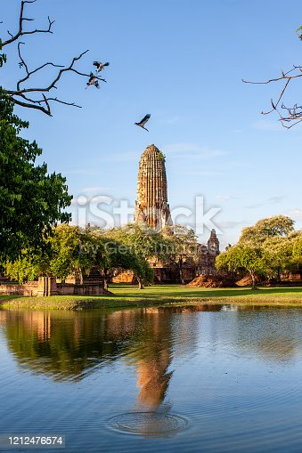 The old ancient chedi of Wat Phra Ram in Ayutthaya's famous historical park is framed by open billed storks, trees and the old water-filled moat surrounding the temple.
