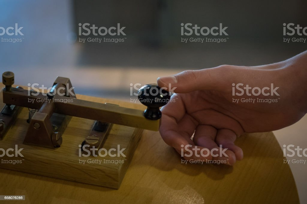 The old and vintage telegraph key and operator's hand royalty-free stock photo