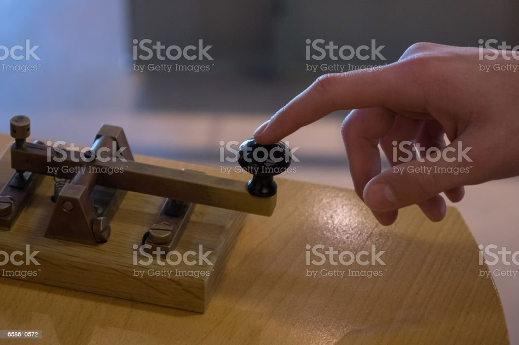 The old and vintage telegraph key and operator's hand stock photo
