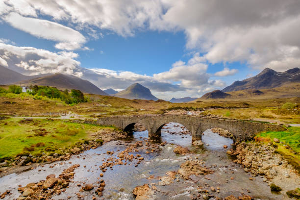 The old bridge of Sligachan with the rocky mountains of Cuillin on the background is one of the iconic images of Skye, the largest and northernmost of the major islands in the Inner Hebrides of Scotland The old bridge of Sligachan with the rocky mountains of Cuillin on the background is one of the iconic images of Skye, the largest and northernmost of the major islands in the Inner Hebrides of Scotland isle of skye stock pictures, royalty-free photos & images