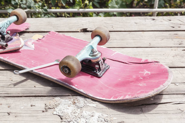 The old broken skateboard lies with a spanner on a wooden table in the open air stock photo