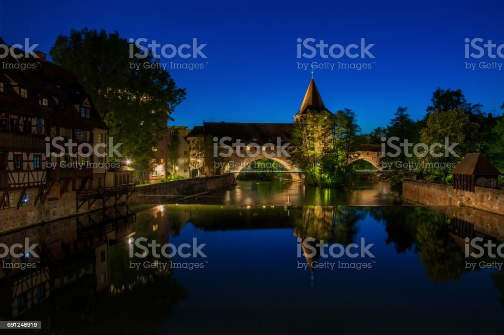 The old chain bridge Kettenssteg and the river Pegnitz in the old town of Nuremberg, Germany during blue hour stock photo
