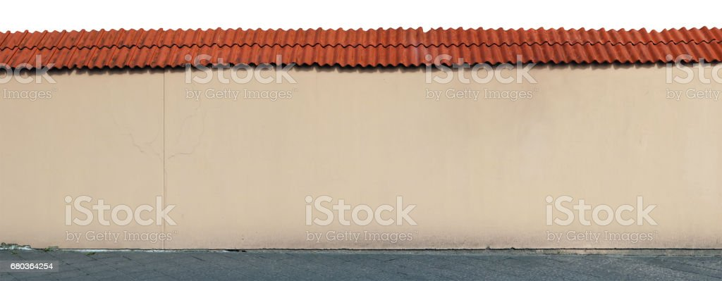 The old church stone wall is covered with yellow plaster. Red clay tiles protects a wall from a rain. Sunny spring day. Isolated panorama from several outdoor photos royalty-free stock photo