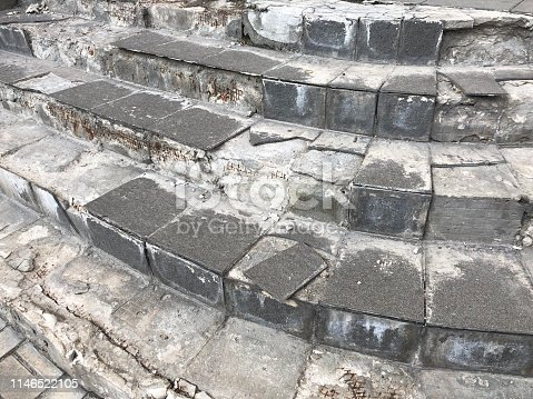 The old concrete stairs with tile surface cracked. Close up on Dangerous Broken House Steps Outdoor. Damaged Stairсase in need of repair