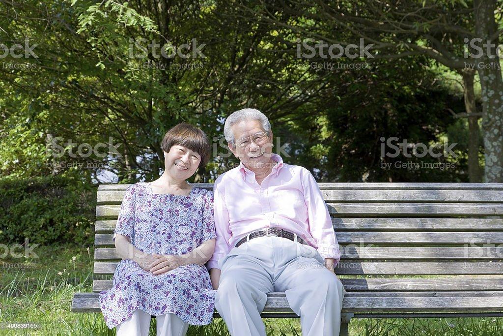 Alte Paar sitzt auf der Bank, die – Foto
