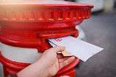 Closeup of an unrecognizable person's hand sliding in letters into a red mailbox outside during the day