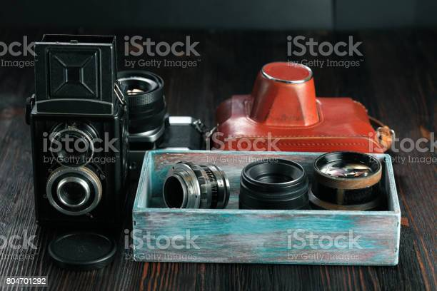 The old film cameras and lenses on the wooden background.