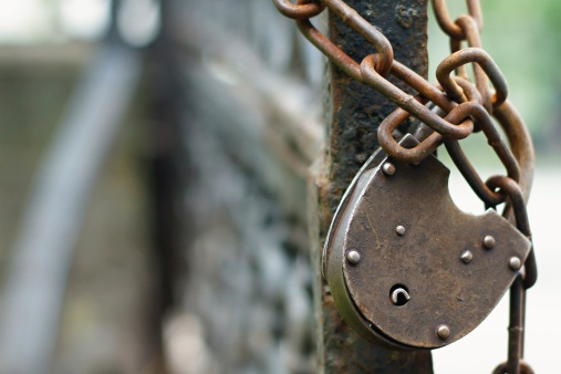 The old lock through a chain weighs on a column of an iron fencing