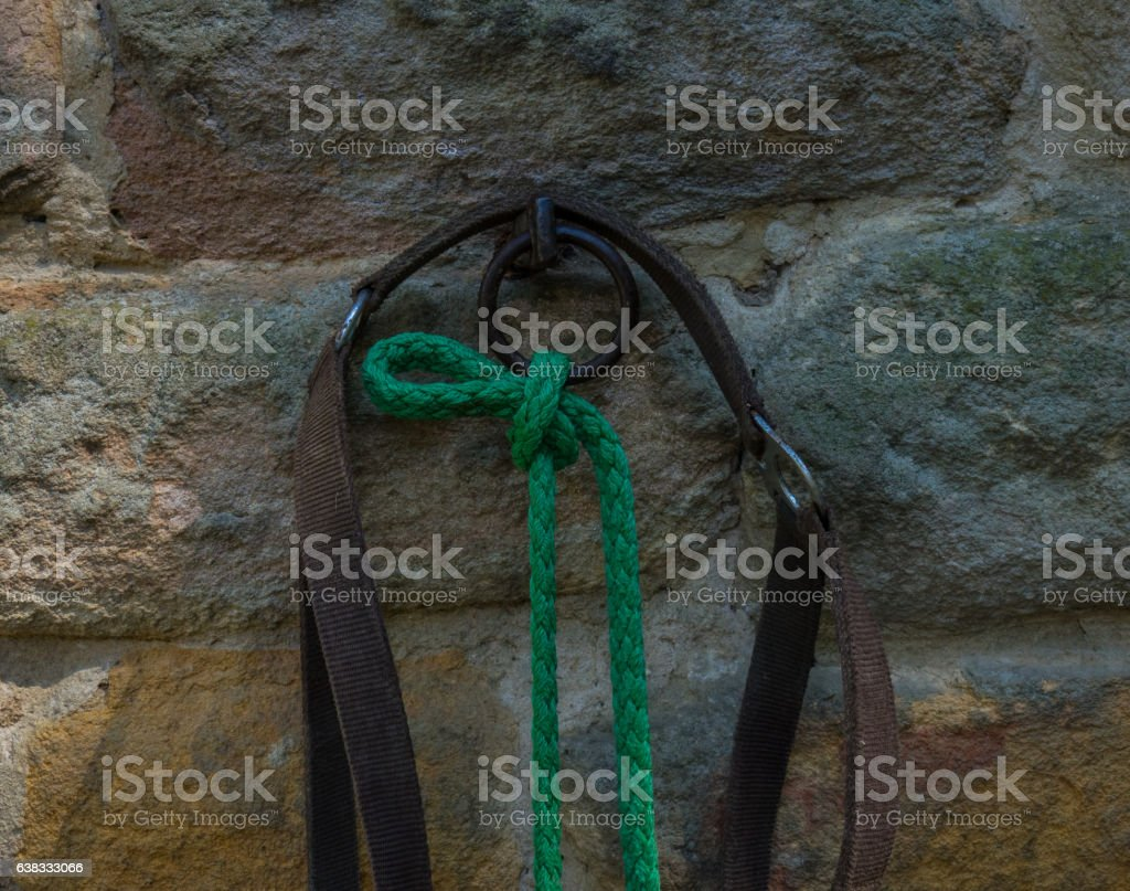 The old hitching post on a stone wall stock photo