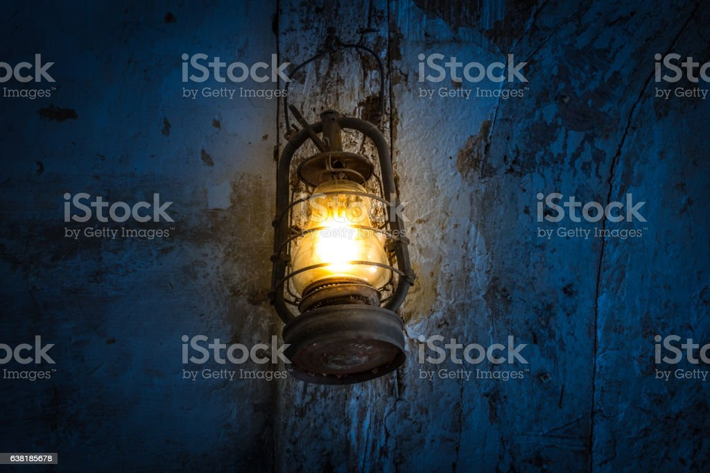 The old kerosene lamp on a wall in dark room stock photo