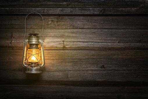 The old kerosene lamp on wooden background