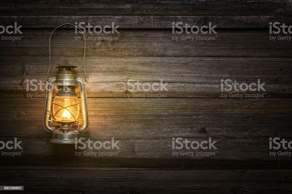 The old kerosene lamp on wooden background stock photo