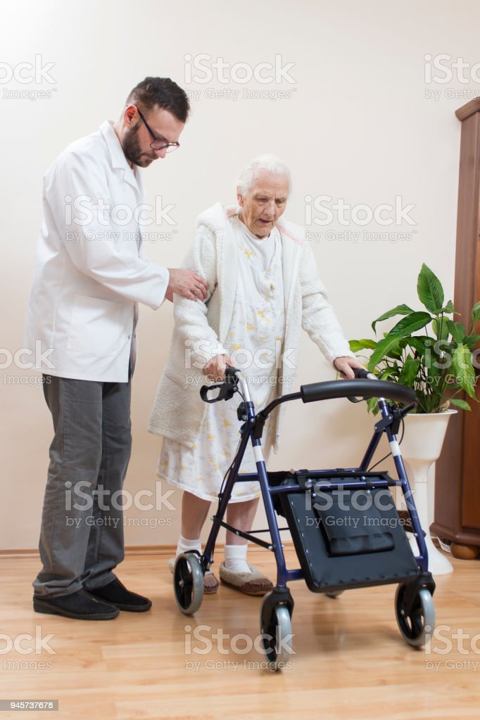 The old lady learns to walk with the help of a rehabilitation balcony at the belaying of a doctor. stock photo