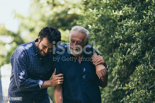 The old man and his son are walking in the park. A man hugs his elderly father. They are happy and smiling
