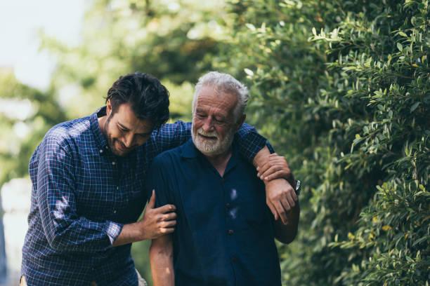 den gamle mannen och hans son går i parken. en man kramar sin äldre far. de är glada och leende - omsorg bildbanksfoton och bilder