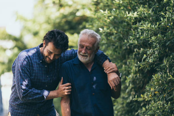 The old man and his son are walking in the park. A man hugs his elderly father. They are happy and smiling The old man and his son are walking in the park. A man hugs his elderly father. They are happy and smiling care stock pictures, royalty-free photos & images
