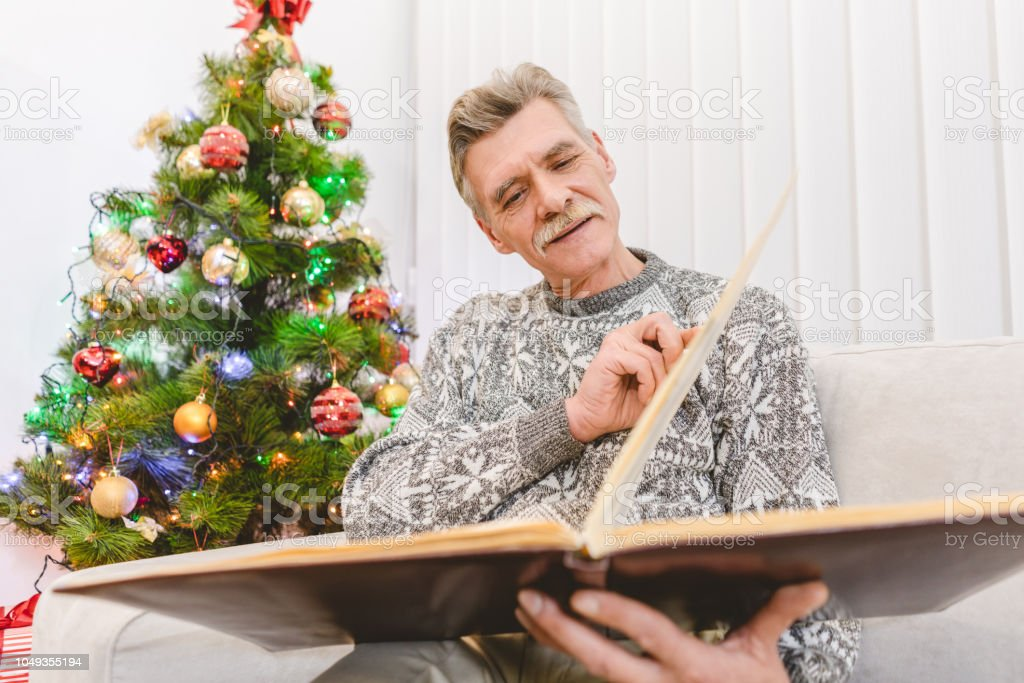 The old man hold a book near the christmas tree