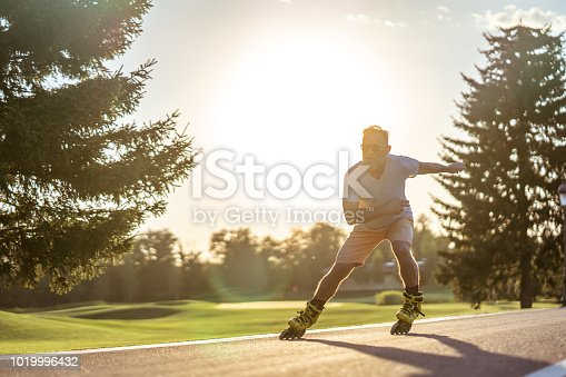 The old man in sunglasses rollerblading on the sunset background