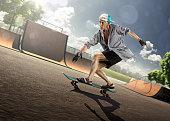 The old man is skating on skateboard in skate park