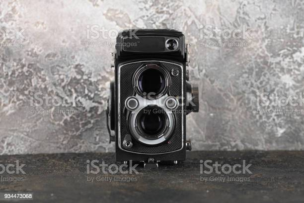 The old medium format film TLR camera on cement background.
