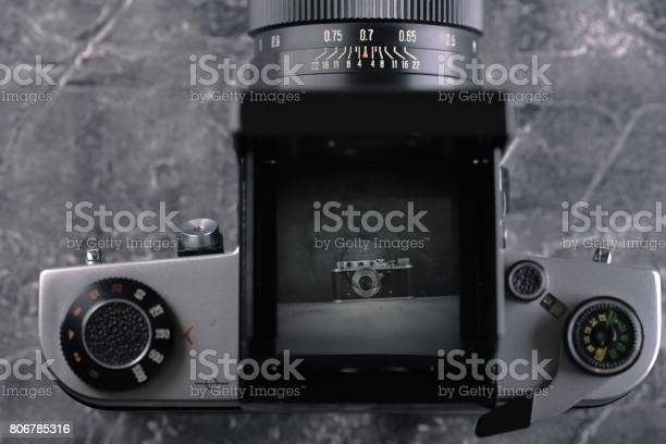 The old Medium format SLR camera on a cement background.
