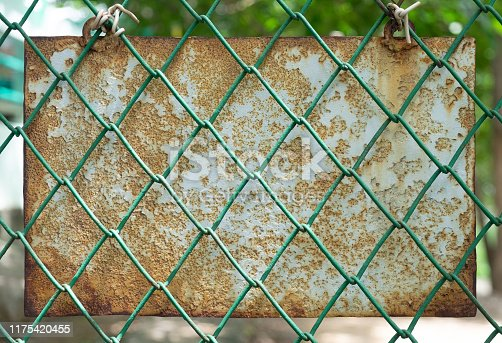 924754302 istock photo The old metal plaque that decayed behind the green mesh cage in the park. 1175420455