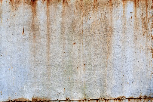 The old metal wall is painted with white paint. Centers of corrosion and rust streaks are visible. Background. Texture.