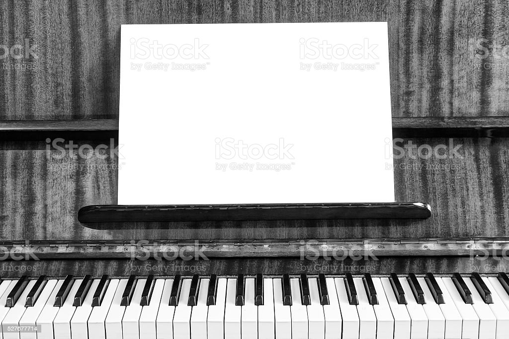 The old piano and sheet of white paper. Close-up view. stock photo