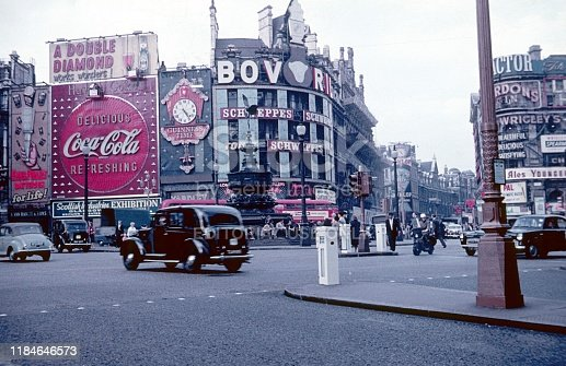 London, England, UK, 1959. The old Piccadilly Circus with the Shaftesbury Memorial Fountain, old buildings and its billboards in the heart of London. Furthermore: pedestrians, traffic and shops.