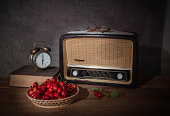 The old radio and fresh cherries on wooden table
