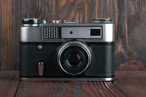 The old rangefinder camera on a brown wooden background.