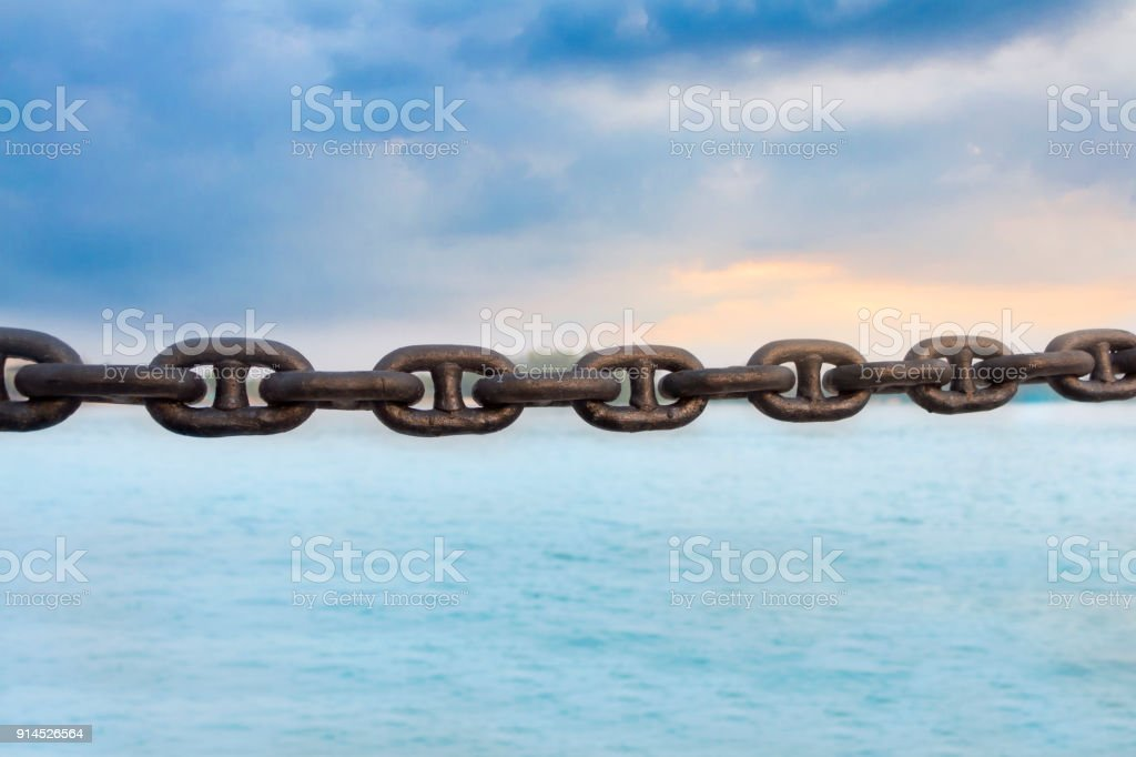 The old rusty chain on sea and sky background. stock photo