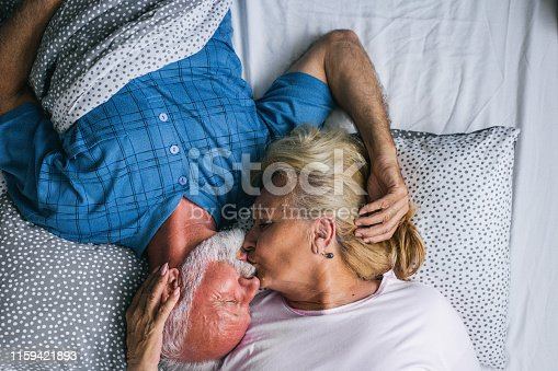 istock The old senior couple are kissing in bed 1159421893