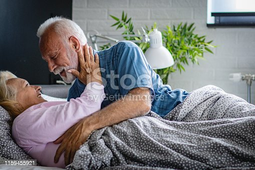istock The old senior couple are kissing in bed 1159455921
