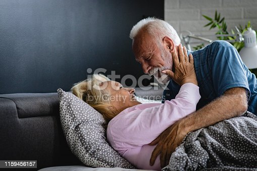 istock The old senior couple are kissing in bed 1159456157